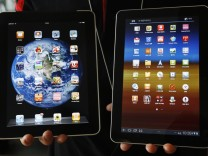 File photo shows an employee of a South Korean mobile carrier holding a Samsung Galaxy tablet and an Apple iPad tablet in Seoul