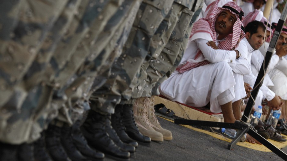 Relatives watch Saudi police cadets during their passing out parade at a base near Riyadh