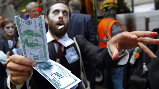 A demonstrator, dressed as a 'corporate zombie' walks with others taking part in an Occupy Wall Street protest in lower Manhattan in New York