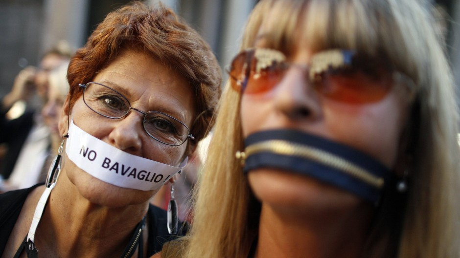 Women, who put a zip and a tape on their mouths, protest against a privacy law in downtown