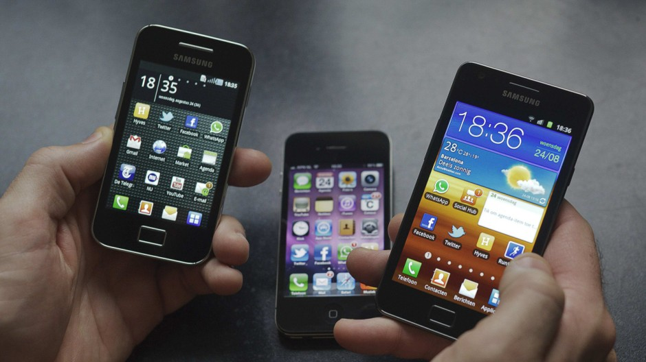 File photo of man holding a Samsung S II and Samsung Ace smartphones next to an Apple iPhone 4 in Houten