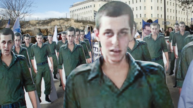 File photo of Noam Shalit standing near cardboard cut-outs of his son Gilad Shalit during protest in Jerusalem