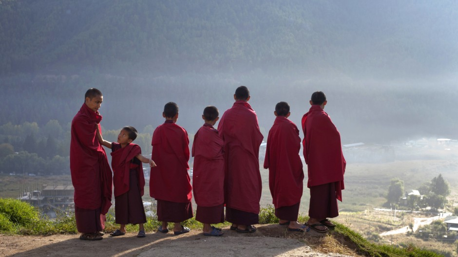 Novice monks at the Dechen Phrodrang Buddhist monastery look down from a hilltop in Bhutan's capital Thimphu