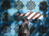 An Iranian woman walks past an anti-U.S. mural on the wall of the former U.S. embassy in Tehran