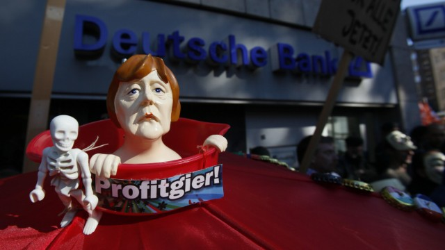 A figure of German Chancellor Merkel is pictured during a protest of several hundred people against banking and finance in front of a branch of Germany's largest bank 'Deutsche Bank' in Cologne