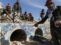 An anti-Gaddafi fighter points at the drain where Muammar Gaddafi was hiding before he was captured in Sirte