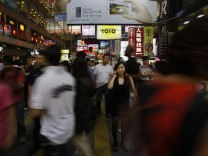 A woman talks on her mobile phone in between pedestrians in Mong Kok district in Hong Kong