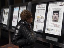 A visitor views front pages of newspapers showing news of Libyan leader Muammar Gaddafi's death on display in front of the Newseum in Washington