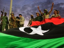 Anti-Gaddafi fighters gesture to the crowds in front of a giant Kingdom of Libya flag during celebrations for the liberation of Libya in Quiche