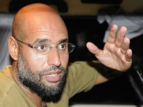 Saif Al-Islam, son of Libyan leader Muammar Gaddafi, gestures as he talks to reporters in Tripoli