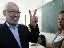 Ghannouchi, the head of the moderate Islamist Ennahda party, gestures after casting his vote at a polling station in Tunisia