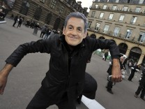 An activist wears a mask portraying France's President Sarkozy during a protest at Palais Royal place in Paris