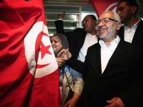 Rachid Ghannouchi, leader of the Islamist Ennahda movement, smiles as he meets his supporters after the announcement of the country's election results, outside his headquarters in Tunis