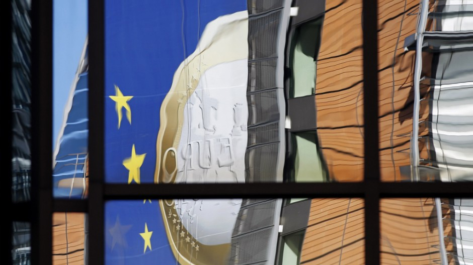 A banner showing a Euro coin is reflected on the facade of the European Commission headquarters in Brussels