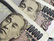 Japanese yen notes are piled atop U.S. dollar bills during a photo opportunity at an office of Interbank Inc. money exchange in Tokyo