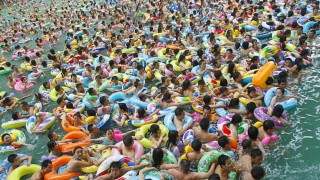 Residents crowd in a swimming pool to escape the summer heat during a hot weather spell in Daying county of Suining