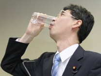 Yasuhiro Sonoda, a cabinet office parliamentary secretary, drinks a water taken from a radioactive puddle from the tsunami crippled Fukushima Daiichi nuclear power plant in Tokyo