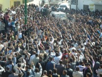 Anti-government protesters shout slogans against Syria's President Bashar al-Assad during the funeral of villagers killed on Wednesday, in Hula