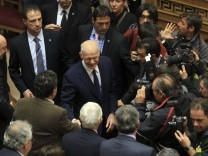 Greek PM Papandreou is surrounded by socialist lawmakers and news photographers before speech to members of parliament from his Socialist party in Athens
