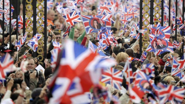 People wave British flags outside Buckingham Palace during the wedding of Britain's Prince William and Kate Middleton at Westminister Abbey, in central London