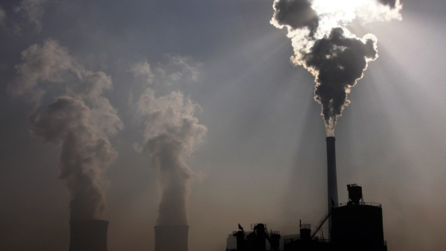 A coal-burning power plant can be seen behind a factory in the city of Baotou, in China's Inner Mongolia Autonomous Region