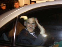 Greek PM George Papandreou waves from his car as he leaves the presidential palace after a meeting with President Karolos Papoulias and Conservative leader Antonis Samaras in Athens
