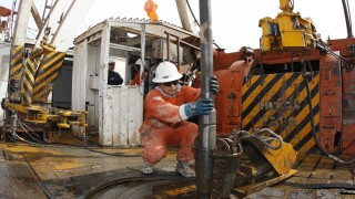 A worker manoeuvres an exploration drill bit at an oil and gas drilling rig in the Patagonian province of Neuquen