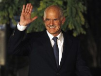 Greek Prime Minister George Papandreou waves to reporters as he arrives at the presidential palace in Athens