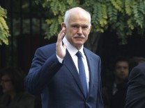 Outgoing Greek Prime Minister George Papandreou waves at reporters as he walks towards the presidential palace in Athens