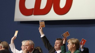German Chancellor Merkel holds up a voting card during CDU party convention in Leipzig
