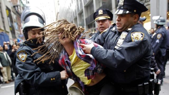 Polizisten nehmen in New York eine Demonstrantin fest.