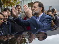 Spain's opposition centre-right People's Party  leader Rajoy waves after casting his vote during a general election in Madrid