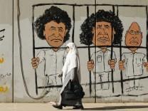 Woman walks past graffiti on wall of former Libyan leader Gaddafi, his son al-Islam Gaddafi and former head of Libyan Intelligence Service Al-Senussi in Tripoli