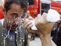 A protester has his eyes washed with milk to protect against tear gas, during clashes with police in Cairo