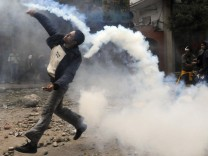 A protester throws a tear gas canister, which had earlier been thrown by riot police, near Tahrir Square in Cairo