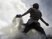 A protester throws a tear gas canister, which was earlier thrown by riot police during clashes along a road which leads to the Interior Ministry, near Tahrir Square in Cairo
