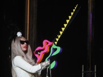 Singer Lady Gaga carries a pair of scissors during a ribbon cutting ceremony to launch Gaga's Workshop at Barneys department store in New York