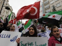Syrians living in Turkey wave Turkish and Syrian flags as they protest against the government of Syria's President Bashar al-Assad after Friday prayers in front of the Syrian consulate in Istanbul