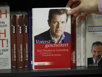 Woman holds copy of latest book by Germany's former defence minister Guttenberg in Berlin