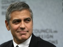 File photo of George Clooney listening to opening remarks in Washington