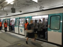 Passengers rush into a train at Saint-Lazare metro station in Paris