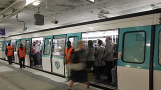 Passengers rush into a train at Saint-Lazare metro station in Paris