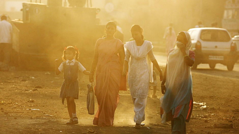 People walk through haze at an industrial area in Mumbai