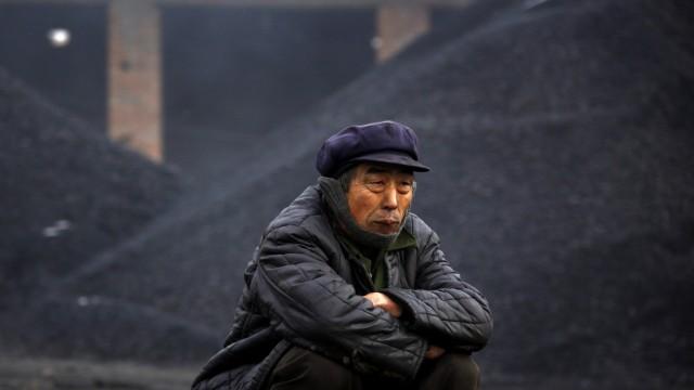 An elderly man takes a break from loading coal onto trucks near the town of Dangcheng