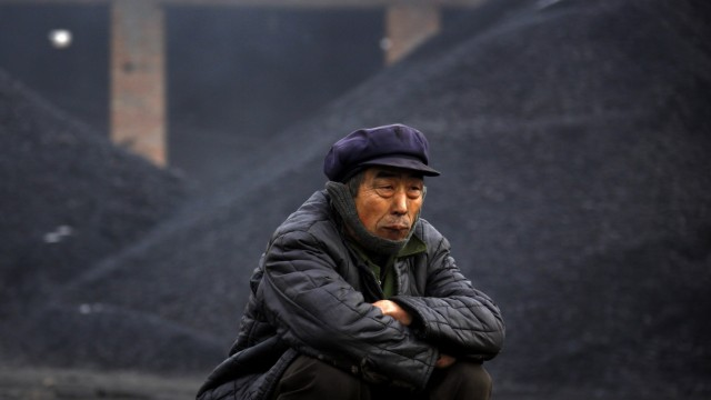 An elderly man takes a break from loading coal onto trucks near the town of Dangcheng
