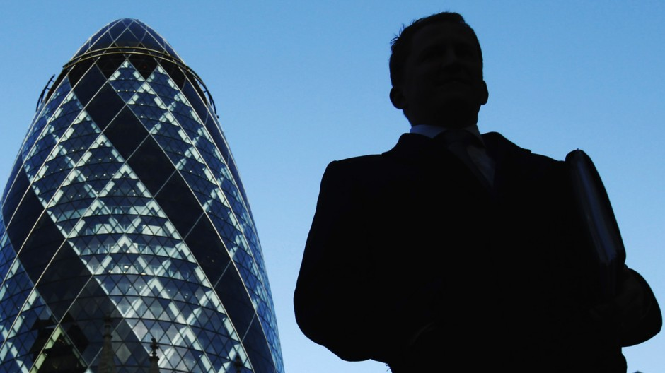 A City worker walks near the Swiss Re building known as the Gherkin in the City of London
