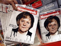 An employee of a store holds up copies of a Newsweek magazine bearing a picture of German Chancellor Angela Merkel for the photographer at the main train station in Berlin