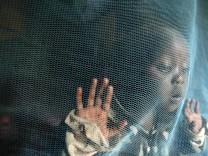 Welt-Malariatag - Kind hinter Moskitonetz