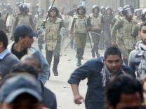 Protesters run during clashes with army soldiers at the cabinet near Tahrir Square in Cairo