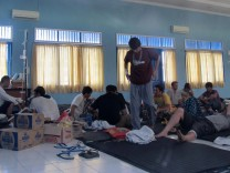 Injured people, who were rescued after their boat sank in East Java, stay at a temporary shelter in Trenggalek